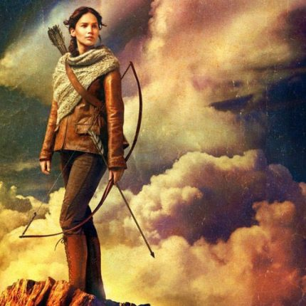 katniss stands on a hill with a bow