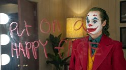 joker looks into a mirror with writing telling him to put on a happy face