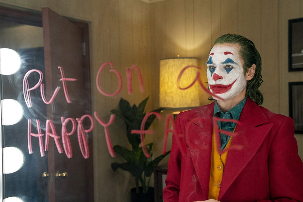 """joker looks into a mirror with writing that reads """"put on a happy face"""""""