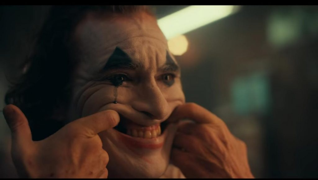 joker hooks fingers in mouth to force smile with tear going down